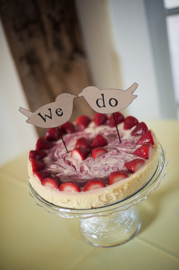a strawberry wedding cheesecake with fresh berries and swirl decor plus funny bird toppers