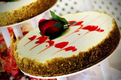 a strawberry wedding cheesecake with swirls and a red rose looks romantic and dramatic