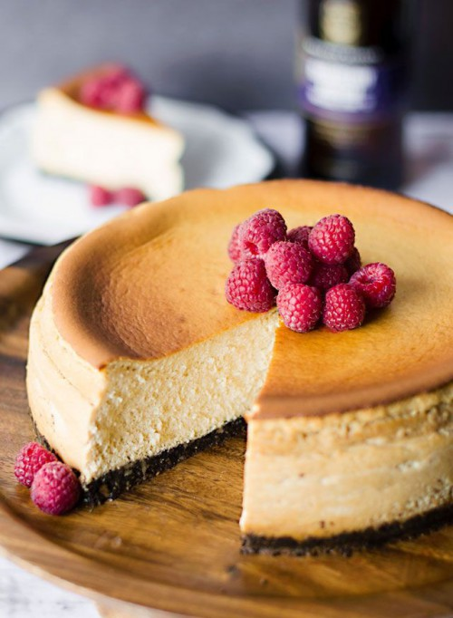 a large wedding cheesecake with chocolate base topped with fresh raspberries