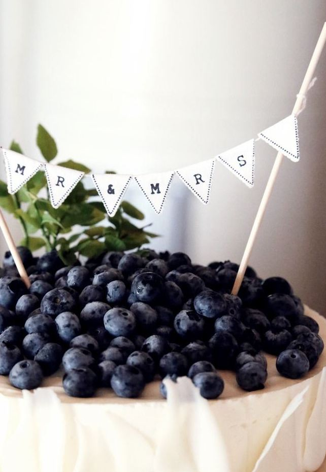 a classic cheesecake decorated with white chocolate petals and lots of blueberries on top plus a banner