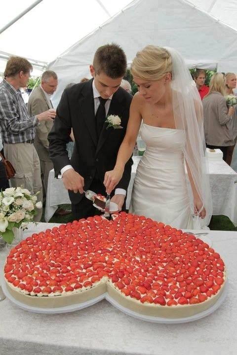 a giant heart-shaped wedding cheesecake covered with strawberries and white chocolate