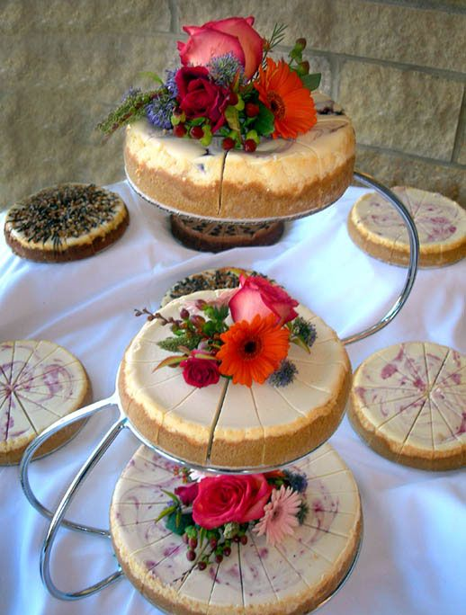 classic and berry swirl wedding cheesecakes topped with fresh blooms in various colors