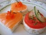 mini sandwiches with cream cheese, salmon, tomatoes and some caviar and fresh herbs on top